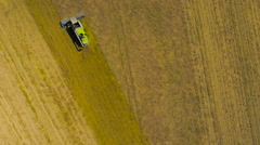 Slow motion birds-eye view aerial drone footage of a Claas combine harvester - stock footage