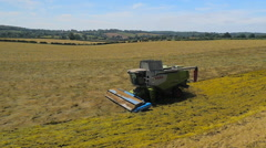 Slow motion wide aerial drone footage of a Claas combine harvester - stock footage