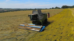 Slow motion aerial drone footage of a Claas combine harvester from the front - stock footage