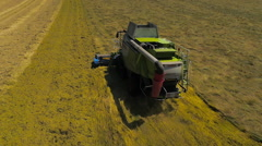 Slow motion aerial drone footage of a Claas combine harvester - stock footage