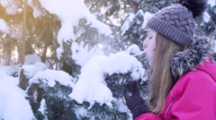Young women playing with fir-tree in snow - stock footage