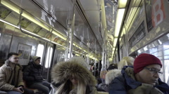 Interior subway car - passengers riding B train in winter in NYC Stock Footage