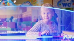 Funny girl playing air hockey Stock Footage