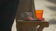A coffee cup and a plastic cup on a chair in Sarajevo Stock Footage