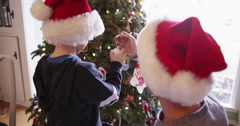 Young caucasian boy helping dad decorate x-mas tree Stock Footage