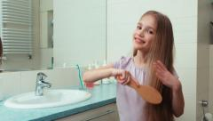 Portrait girl 7 years old preening before the mirror in the bathroom and smiling Stock Footage