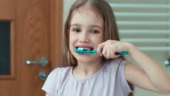 Closeup portrait child 7 years old brushing her teeth with a toothbrush Stock Footage