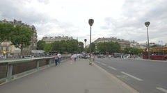 People walking, cars driving and tricycles riding on a bridge in Paris Stock Footage