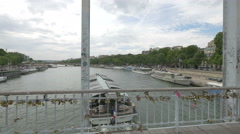 Moored boats and boat sailing on Seine seen from Passarelle Debilly in  Paris Stock Footage