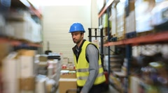 Warehouse operator pulling cart in storage aisle Stock Footage