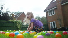 Stock Video Footage of 4K Little girl & mother playing in garden with lots of coloured plastic balls