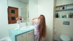 Portrait girl 7 years old preening long beautiful hair before the mirror Stock Footage