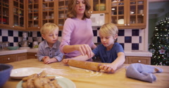Cute young caucasian child blending cookie dough with mom and brother Stock Footage