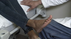 Tight shot of a doctor checking woman's ankle. - stock footage