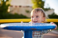 Baby boy child plays in playground area - stock photo