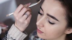 A cute model gets makeup put on. Close up shot Stock Footage