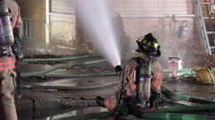 Firefighter Sprays Water on Fire Stock Footage