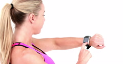 Smiling sportswoman uses her smart watch Stock Footage