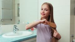 Portrait girl 7 years old preening before the mirror in the bathroom Stock Footage