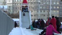 CHILDREN IN ICE TOWN MOVE DOWN FROM ICE SLIDE. CHELYABINSK, RUSSIA. 2 Stock Footage