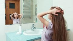 Portrait girl child 7 years old preening before the mirror in the bathroom Stock Footage