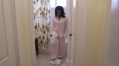 Pajamaed woman in bathroom weighing herself. - stock footage