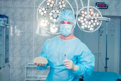 Surgeon at operating room in the hospital. breast augmentation - stock photo