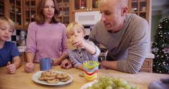 Beautiful white family eating cookies and milk together Stock Footage