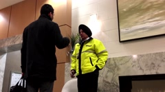 Security guy talking to the resident inside apartment lobby Stock Footage