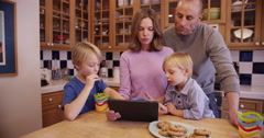 Two lovely caucasian parents eating cookies and reading a tablet with children - stock footage