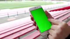 Woman holds a blank smart device with a green screen Stock Footage