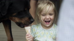 Dog comes from behind licking a girl's icecream cone. Stock Footage
