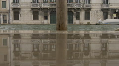 Old building and wooden post reflecting in a puddle of water, Venice Stock Footage