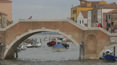 Boats passing under a brick bridge while tourists are walking on it in Venice Stock Footage