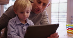 Adorable young white boy learning to use tablet computer Stock Footage