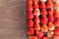 red ripe strawberry in plastic box of packaging on wood table - stock photo