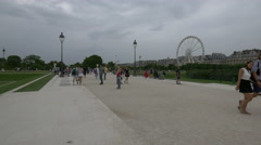 People walking in Tuileries Garden on a cloudy day in Paris Stock Footage