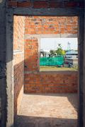 wall made brick and door structure in residential building construction site - stock photo