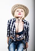 Young beautiful sexy woman in a plaid shirt jeans and a cowboy hat - stock photo