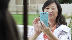Mother taking a picture of her daughter wearing graduation cap. - stock footage