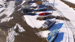 Sailboats in winter storage, frozen marina in winter, Aerial Flyover Stock Footage
