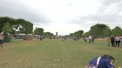 People sitting, walking and taking pictures in Champ de Mars in Paris - stock footage