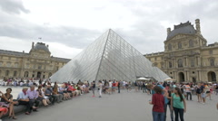 Tourists sitting next to the Louvre Pyramid in the Napoleon Courtyard, Paris Stock Footage
