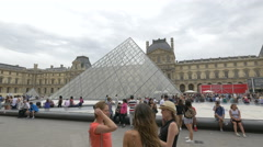 Leisure time next to the Louvre Pyramid in the Napoleon Courtyard, Paris Stock Footage