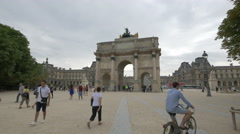 People walking and riding bicycles near the Louvre Gate, Paris Stock Footage