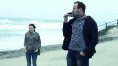 Young offended couple after fight standing on the beach on a stormy day Stock Footage