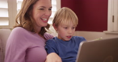 Handsome young boy looking at a laptop computer screen with mom Stock Footage