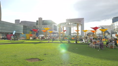 People relaxing and children playing on grass in La Défense, Paris Stock Footage