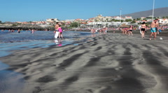 People rest and play on black sandy beach at Atlantic. Playa Fanabe, Tenerife Stock Footage