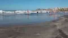 Black sandy beach is washed with Atlantic ocean. Costa Adeje, Tenerife Stock Footage
